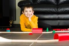 Dzieciak chłopiec bawić się z drewnianymi pociągami zdjęcie royalty free