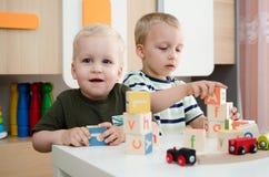 Dzieciak chłopiec bawić się z zabawkarskimi blokami lub dziecinem w domu zdjęcie royalty free