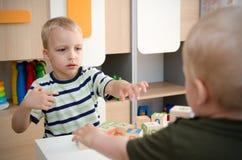 Dzieciak chłopiec bawić się z zabawkarskimi blokami lub dziecinem w domu obraz stock