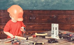 Dzieciak chłopiec młotkuje gwóźdź w drewnianą deskę Dziecko w zbyt dużego hełma śliczny bawić się jako budowniczy lub naprawiacz, zdjęcie stock