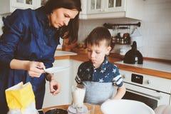 Dzieciak chłopiec pomocy matka gotować w nowożytnej białej kuchni Fotografia Royalty Free