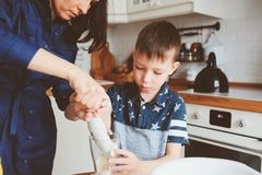 Dzieciak chłopiec pomocy matka gotować w nowożytnej białej kuchni Obrazy Royalty Free
