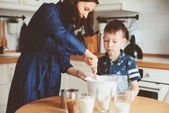 Dzieciak chłopiec pomocy matka gotować w nowożytnej białej kuchni Fotografia Stock