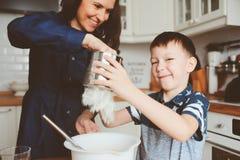 Dzieciak chłopiec pomocy matka gotować w nowożytnej białej kuchni Zdjęcia Stock