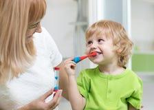 Dzieciak chłopiec szczotkuje zęby w łazience Jego macierzysta monitorowanie dokładność i czas cleaning akcja z hourglass obraz stock