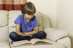 Dzieciak czyta książkę w domu fotografia stock