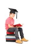 Dzieciak czyta książkę z mortarboard zdjęcie royalty free
