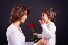 Dzieciak daje wspaniałej czerwieni róży jego mama Zdjęcie Stock