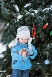Dzieciak dekoruje choinki plenerowej w zima parku Prezenty i choinki Zdjęcia Stock