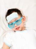 Dzieciak dołącza chłodniczego gel ochraniacza na jego czole Obrazy Royalty Free