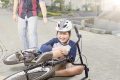 Dzieciak dostaje wypadek z jego płaczem i rowerem obraz royalty free