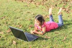 Dzieciak - dziewczyna bawić się z notatnikiem obraz royalty free