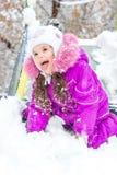 Dzieciak dziewczyna na dzieciach ono ślizga się przy śnieżnym zima dniem Zdjęcia Stock