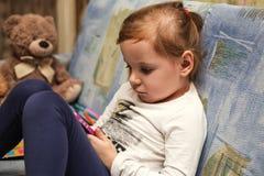Dzieciak dziewczyna patrzeje smartphone ekran fotografia royalty free
