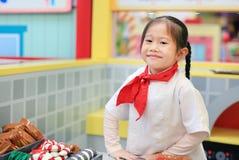 Dzieciak dziewczyna w kostiumu mały szef kuchni robi pizzy, Kulinarny dziecka pojęcie obrazy royalty free
