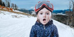 Dzieciak dziewczyna w narciarskiej przekładni na zimy tle Obrazy Stock