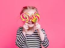 Dzieciak dziewczyna z lollypops w przodzie ona oczy Zdjęcie Royalty Free
