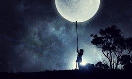 Dzieciak dziewczyny chwytająca księżyc Fotografia Stock