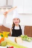 Dzieciak dziewczyny szef kuchni na countertop śmiesznym gescie z rolownikiem ugniata Obraz Royalty Free