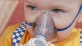 Dzieciak himself trzyma maskę od inhalatoru i oddycha medycynę w domu Taktuje rozognienie drogi oddechowe przez zbiory