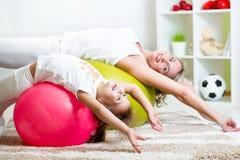 Dzieciak i matka robimy gimnastycznym ćwiczeniom z gumową piłką przy hom Obraz Stock