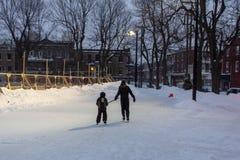 Dzieciak i potomstwo dorosły bawić się wpólnie na łyżwach podczas gdy przy lodowiskiem w jawnym parku - 1/2 zdjęcia royalty free