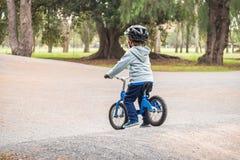 Dzieciak jazdy równowagi rower w parku zdjęcia royalty free