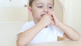Dzieciak je czekoladowego lody rożek z przyjemnością w gofra rożku, siedzi przy stołem Dziecko jest szczęśliwy zbiory wideo