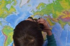Dzieciak jest przyglądający przez lornetek wokoło Przygody i podróży pojęcie Radosny tło Dziecko bawić się w jego pokoju zdjęcie royalty free