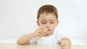 Dzieciak jest szczęśliwy jeść czekoladowego rożek lody w gofra rożku, siedzi przy stołem na białym tle, zbiory wideo