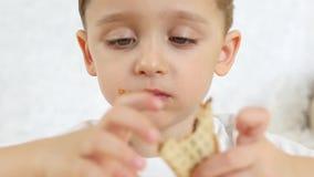 Dzieciak jest szczęśliwy jeść czekoladowego rożek lody w gofra rożku, siedzi przy stołem na białym tle, zakończenie zdjęcie wideo