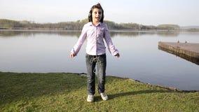 Dzieciak kochająca muzyka blisko jeziora zbiory wideo