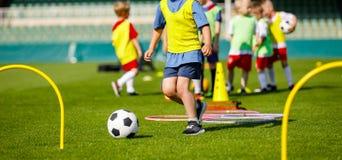Dzieciak Młode atlety Trenuje z Futbolowym wyposażeniem Futbolowy prędkości i zwinności szkolenie zdjęcie stock