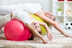 Dzieciak matka i dziewczyna robimy gimnastycznemu wpólnie indoors Fotografia Stock