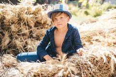 Dzieciak na jesień wakacje w gospodarstwie rolnym Żartuje chłopiec trzyma złocistego liść i kłamstwa na sianie Walkoweru lato - c obrazy royalty free