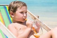 Dzieciak na plażowym pije soku od szklanego kubka z słomą Zdjęcia Royalty Free