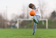Dzieciak piłki nożnej futbol - dziecko gracza dopasowanie na boisko do piłki nożnej zdjęcie stock