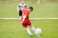 Dzieciak piłki nożnej futbol - dziecko gracze dopasowywają na boisko do piłki nożnej Zdjęcie Royalty Free