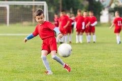 Dzieciak piłki nożnej futbol - dziecko gracze dopasowywają na boisko do piłki nożnej Fotografia Royalty Free