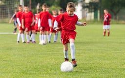Dzieciak piłki nożnej futbol - dziecko gracze dopasowywają na boisko do piłki nożnej Obrazy Royalty Free