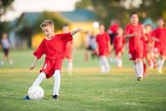 Dzieciak piłki nożnej futbol - dziecko gracze dopasowywają na boisko do piłki nożnej zdjęcia royalty free