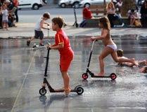 Dzieciak przejażdżki na hulajnoga wśród fontann Zdjęcia Royalty Free
