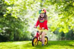 Dzieciak przejażdżki równowagi rower w parku Obrazy Royalty Free