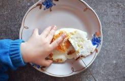 Dzieciak ręka i smażący jajko w talerzu Obraz Stock