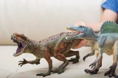 Dzieciak ręki łapie brown Carcharodontosaurus i popielatego Spinosaurus bawją się na kanapie Zdjęcia Stock