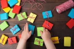 Dzieciak ręki które stawiają kolorowych prezentów pudełka na stole lub dają Zdjęcia Stock
