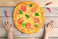 Dzieciak ręki trzymają serową margarita pizzę z pomidorami i basilem, weganinu posiłek na drewnianym wieśniaka stole, odgórny wid fotografia stock