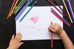 Dzieciak ręki z ołówkiem rysują serce na białej księdze Macierzysty ` s dnia pojęcie Świętowanie Ręcznie robiony karta Odgórny wi obrazy stock