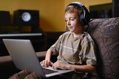 Dzieciak słucha muzyka i wyszukuje internet obraz stock
