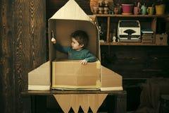 Dzieciak siedzi w kartonowej ręcznie robiony rakiecie Dzieciństwa pojęcie Chłopiec sztuka z rakietą w domu, mały kosmonauta siedz fotografia stock